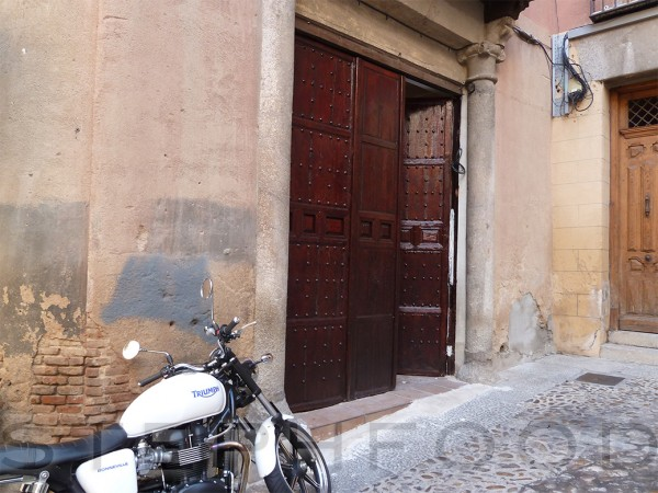 A motorycle against a wall, in Toledo.